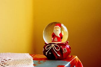 Red Santa Claus water globe on top of red and blue tablecloth