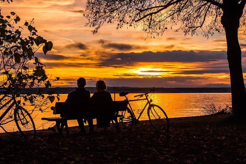 Silhouette of couple sitting on bench near body of water during golden hour
