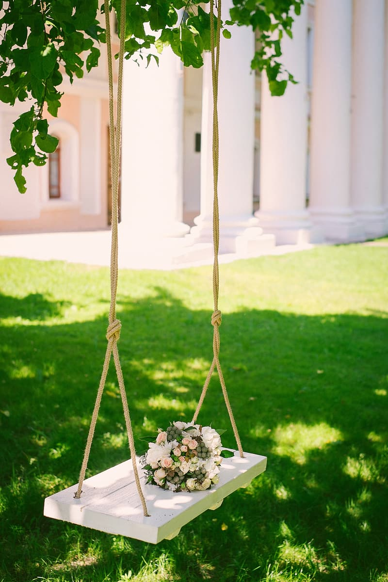 White wooden swing with bouquet of white and pink flowers