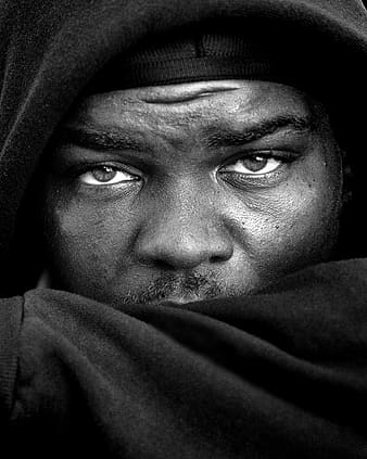 Grayscale photo of man's face wearing hooded jacket