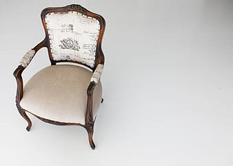 Photo of brown wooden framed white padded armchair