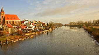 Brown and white houses beside river under cloudy sky during daytime