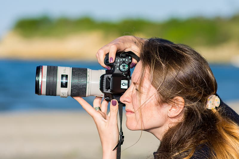 Woman holding black and grey DSLR camera while taking pictures