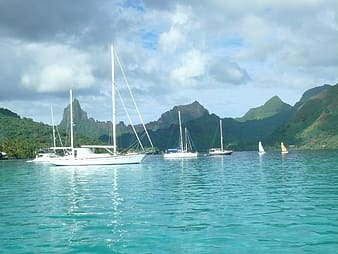 Sailing boats on blue sea surrounded by mountains