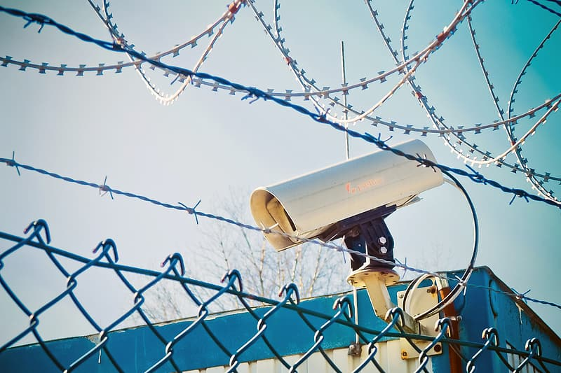 White security camera behind of wire fence during daytime