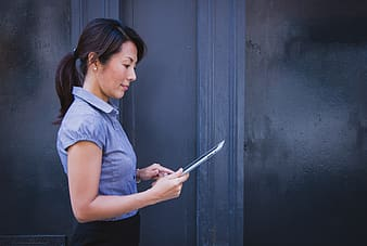 Woman in gray collared shirt holding tablet computer