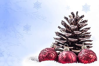 Pine cone and three baubles on snow wallpaper