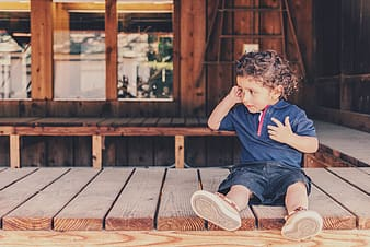 Boy in blue shirt sitting on wooden dock during daytime