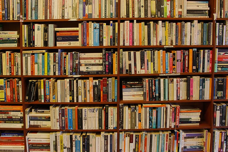 Assorted books piled on brown wooden book case