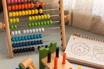 Multi-colored abacus beside printed notebook