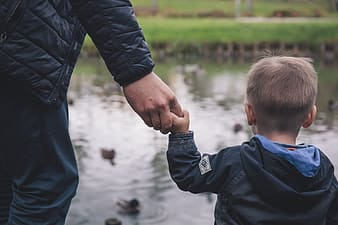 Boy and man holding hands together while feeding ducks on river at daytime