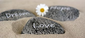 Selective focus photography of black and gray Love-printed stone