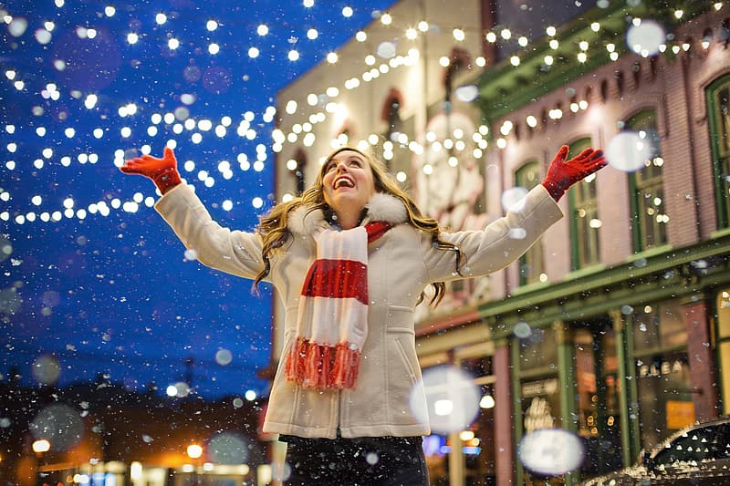 Woman wearing white coat and white and red scarf smiling under falling snow