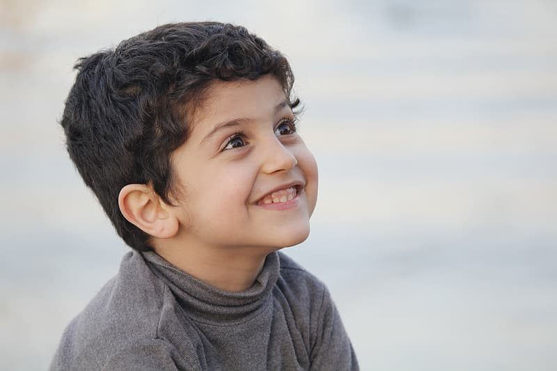 Selective focus photography of a smiling kid