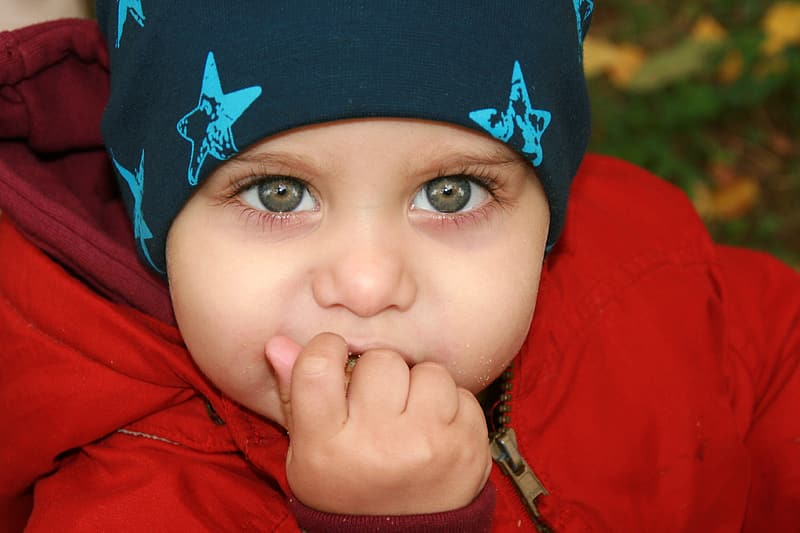 Boy in red hoodie wearing blue and white star print knit cap