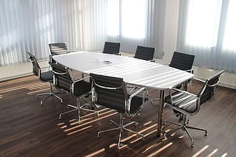 White wooden table with eight armchairs