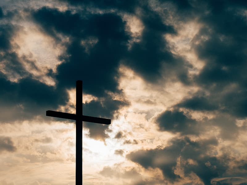 Silhouette photo of wooden cross under gray cloudy sky