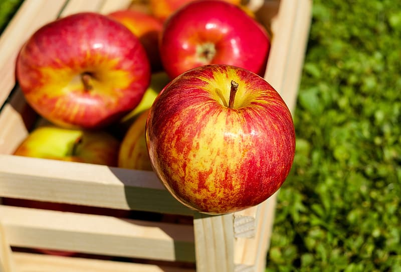 Selective focus photo of an apple on brown wooden crate