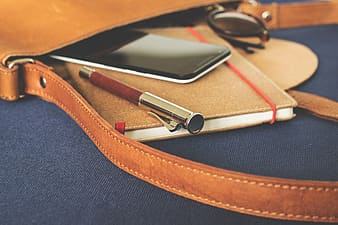 Brown and gray case pen on brown notebook