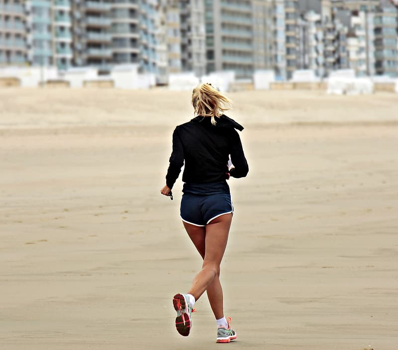Woman wearing black long-sleeved top and blue boy shorts on a early jog