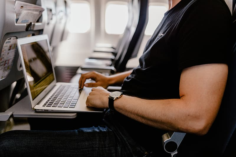 Unrecognizable man with notebook sitting inside an airplane