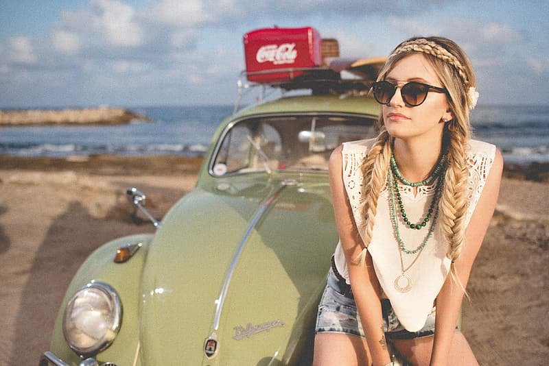 Woman sitting in front of green Volkswagen Beetle on beach sand during daytime