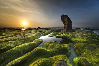 Aerial photography of green and brown rock formation near body of water at golden hour