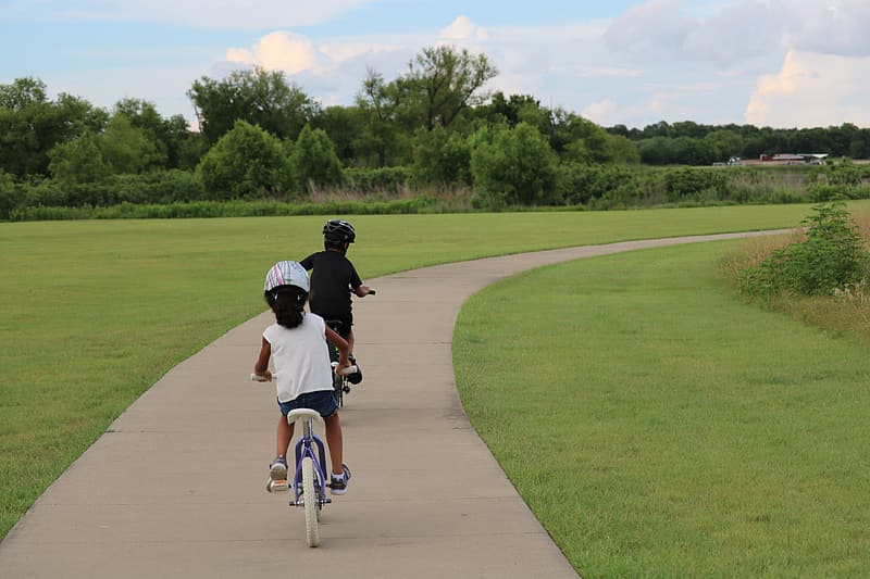 Boy and girl riding bicycles during daytime