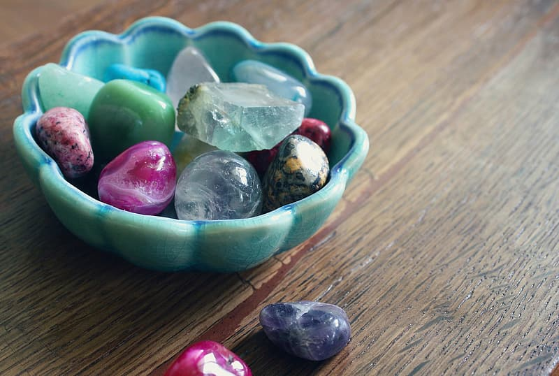 Assorted-color rock collection on and beside teal ceramic bowl