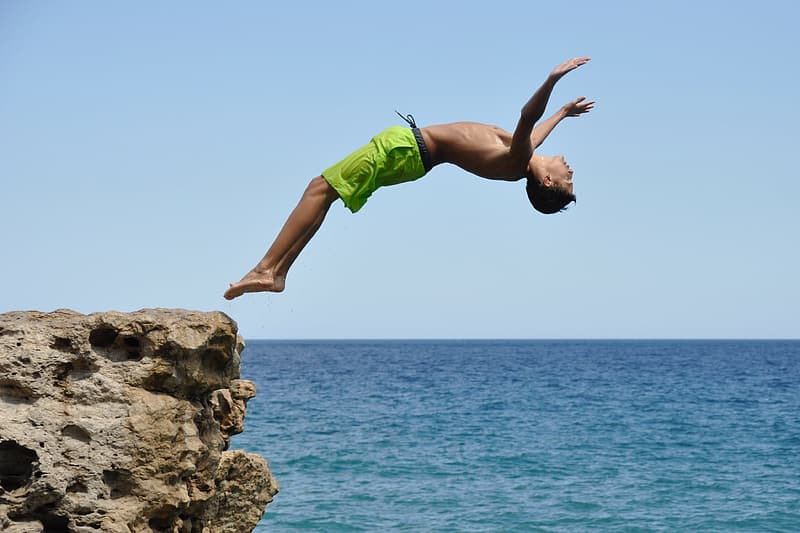 Time lapse photography of man jumping off the cliff