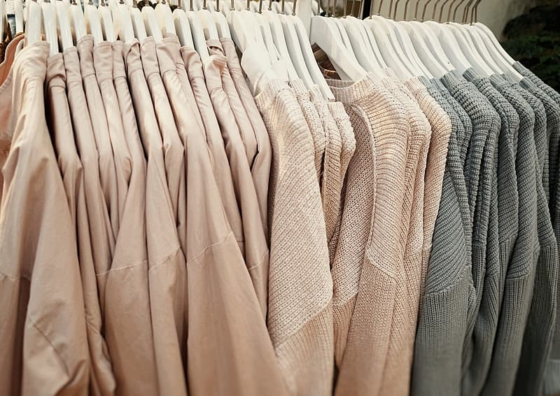 Beige and gray hanging tops with hangers on rack