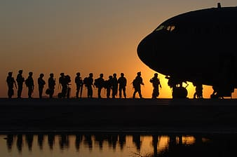 Silhouette of people falling in line in front of plane