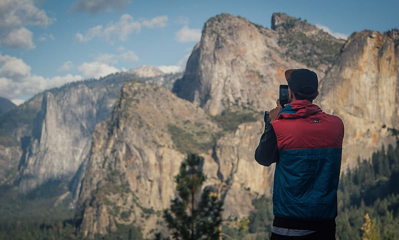 Man standing on ground taking picture of mountain formation during daytime