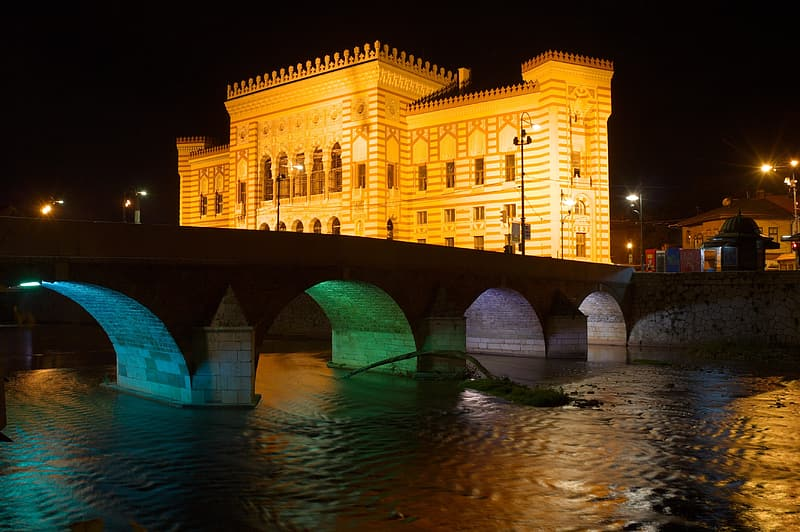 Photography of gray concrete arch bridge near brown concrete building at nighttime