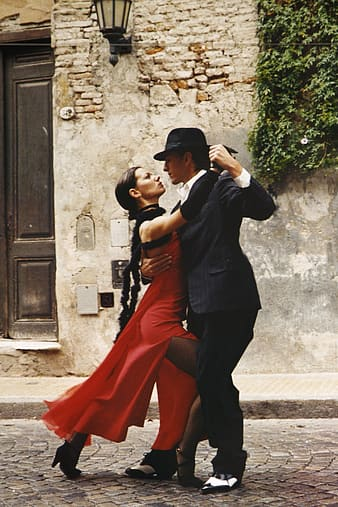 Man in black suit and woman in red slit dress dancing beside grey concrete wall