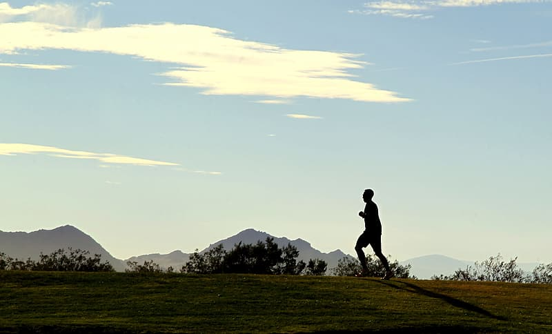 Silhouette of man running on top of hill under white clouds at daytime