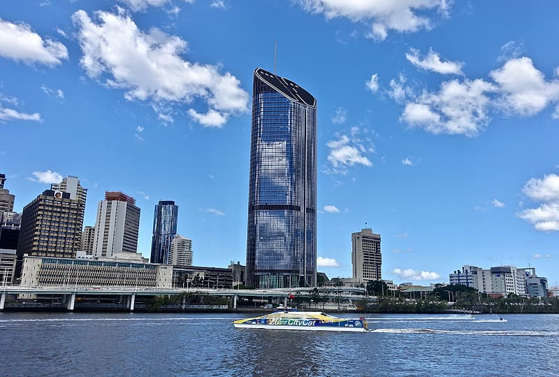 Glass high-rise building near body of water at daytime
