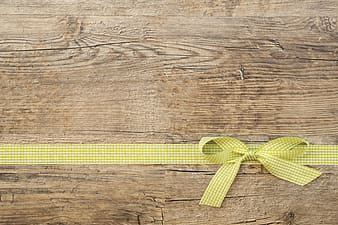 Yellow and white plaid ribbon lace on brown wooden surface