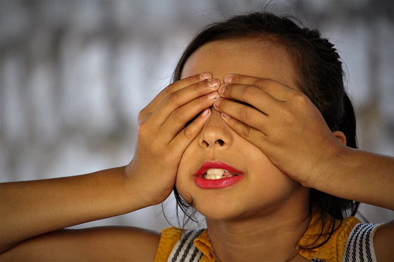 Girl in yellow and white stripe tank top covering her face with her hands