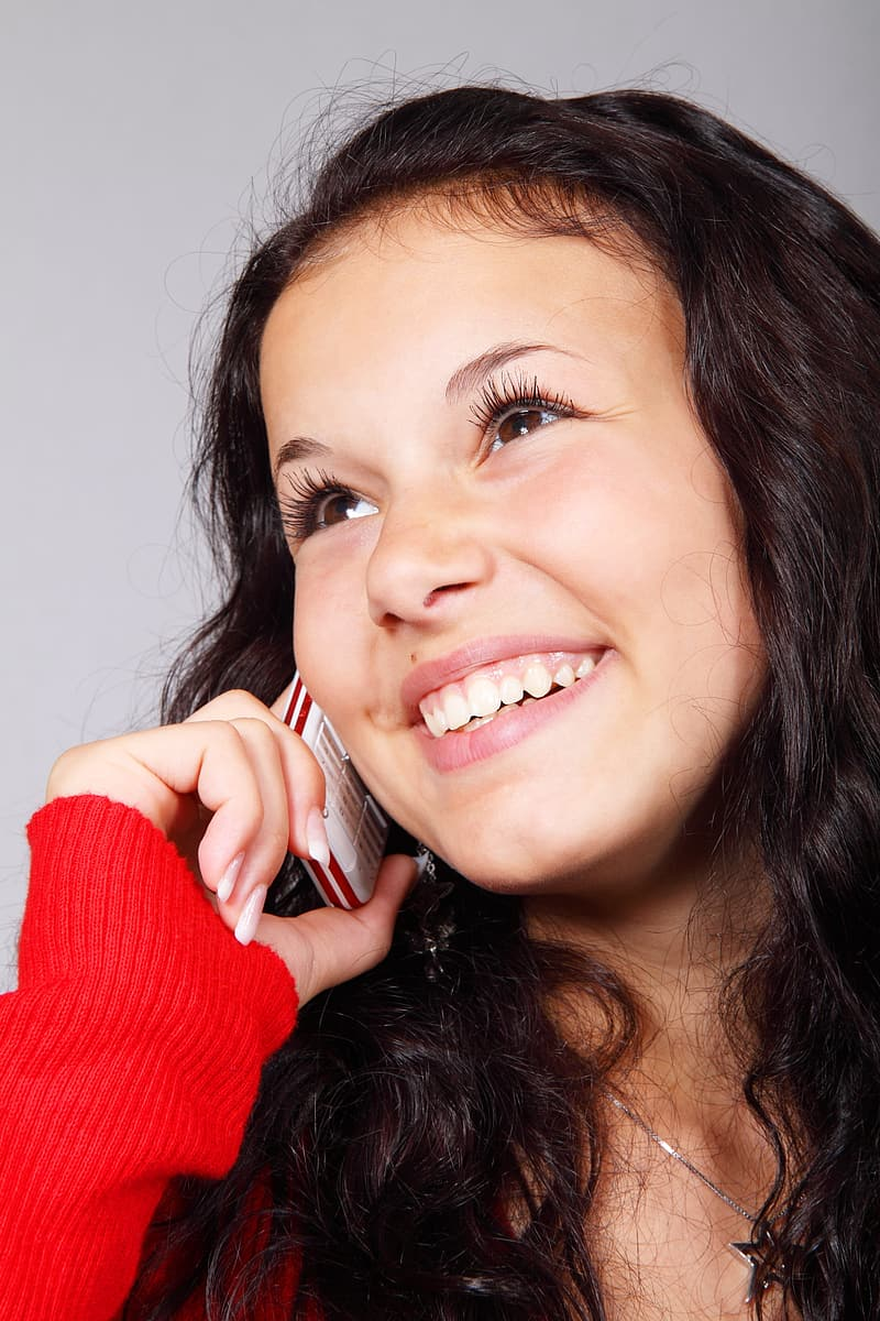 Woman wearing red sweater holding white candybar phone