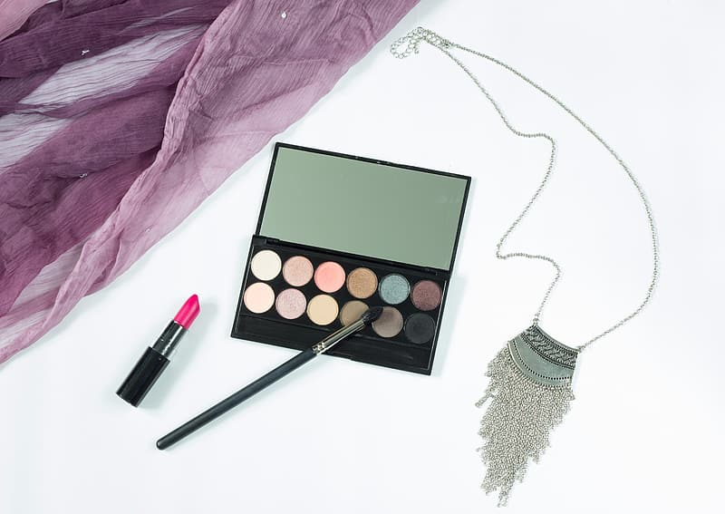 Black eyeshadow palette with pink lipstick and brush