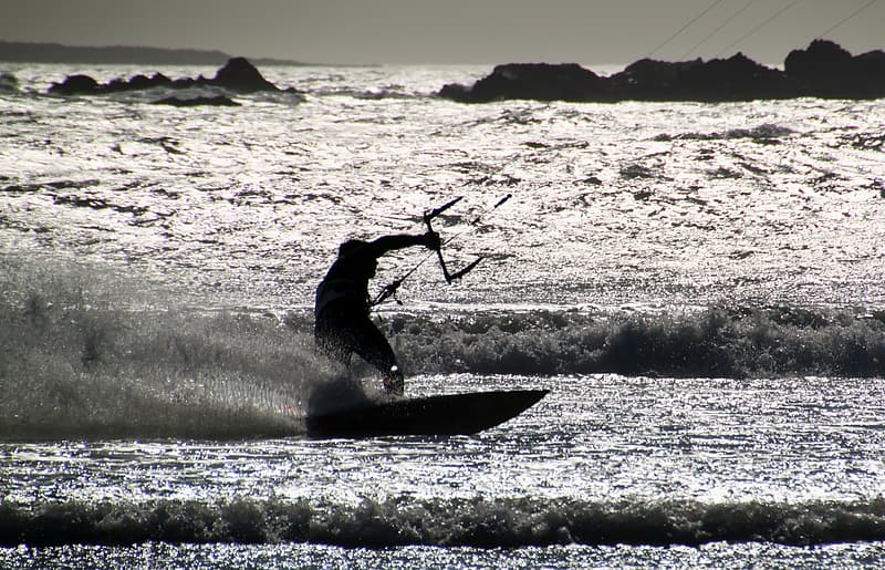 Gray scale photography of man riding on surfboard