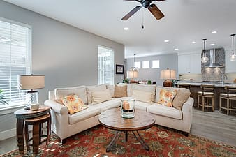 White leather corner sofa on area rug inside house
