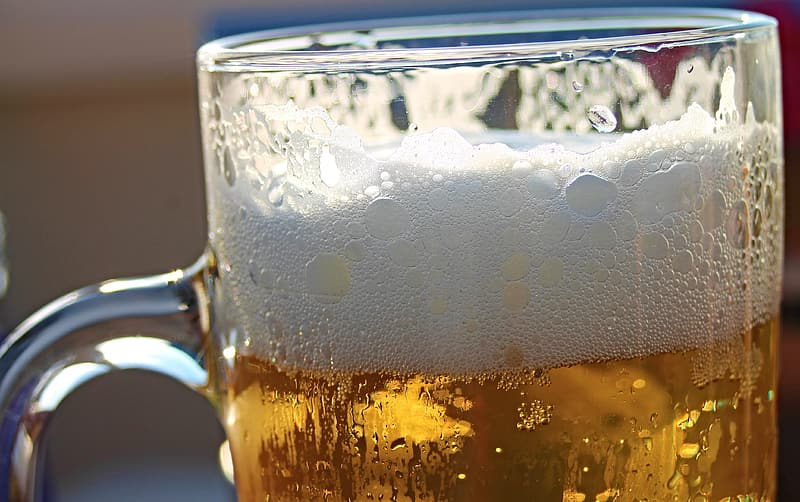 Clear glass beer mug filled with beer close-up photo