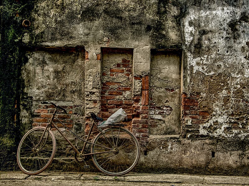 Brown and grey bicycle parked near brown concrete building