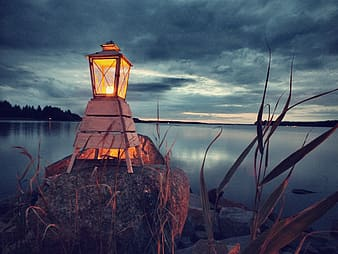 Lighted brown candle lamp on gray stone overlooking still body of water under cloudy sky during daytime