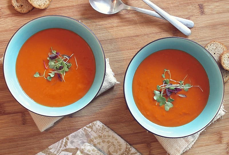 Two bowls of tomato garnished soup