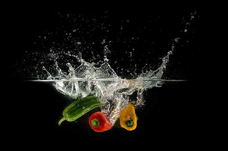 Photo of three assorted-color bell peppers dropped in body of water