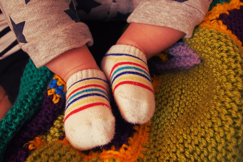 Baby wearing pair of red-blue-yellow-and-white socks