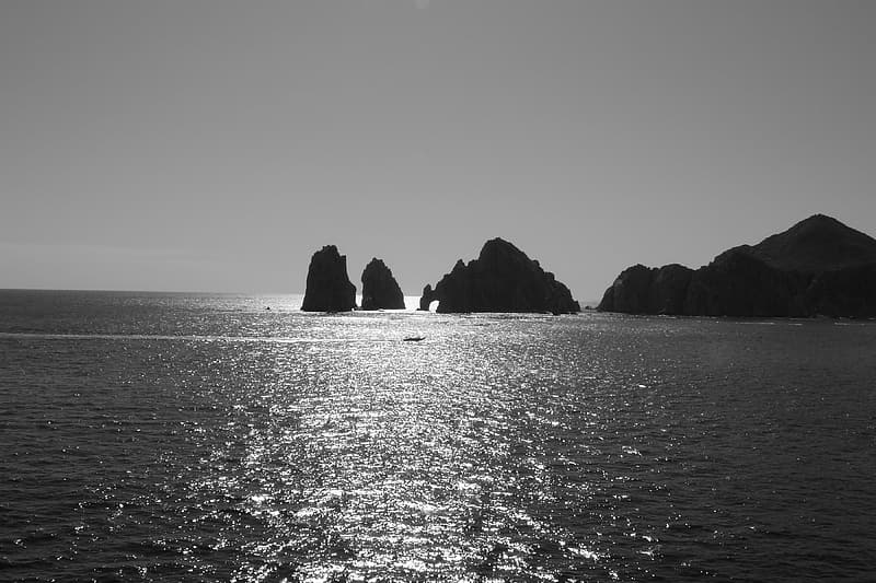Grayscale photo of rock formations surrounded by body of water